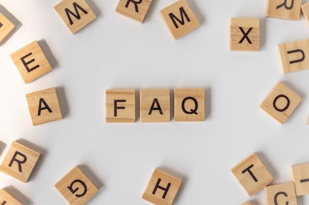 Preguntas frecuentes de redacción de bloque de letras de madera con otras letras en blanco.