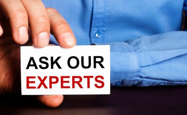 Pregunte a nuestros expertos está escrito en una tarjeta de presentación blanca en la mano de un hombre