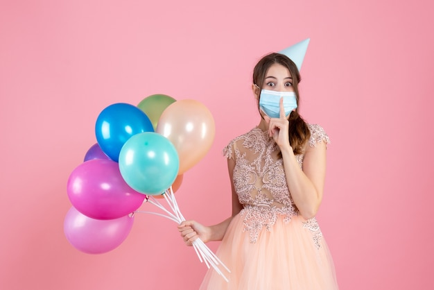 Se preguntó niña con gorro de fiesta y máscara médica haciendo un cartel de shh sosteniendo globos de colores en rosa