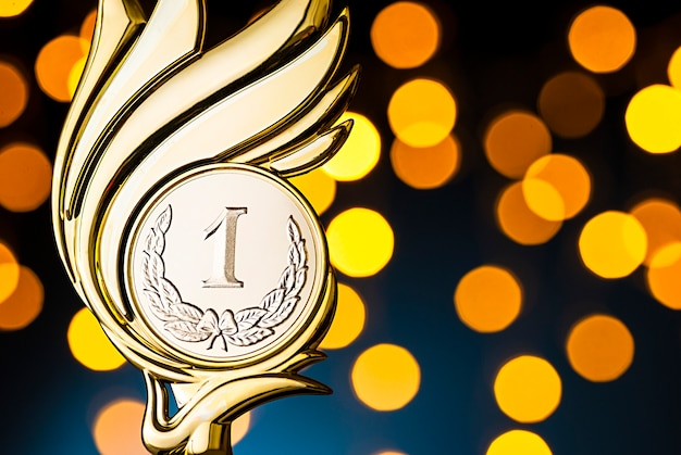 Premio trofeo de oro con evento de medallón en llamas sobre un fondo azul.