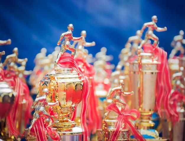 Premios de taza de trofeo de atletas con una cinta roja.