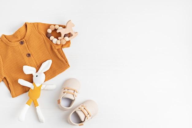 Prenda y accesorios de bebé neutros en cuanto al género. ropa de algodón orgánico, moda recién nacida, branding, idea de pequeña empresa. endecha plana, vista superior