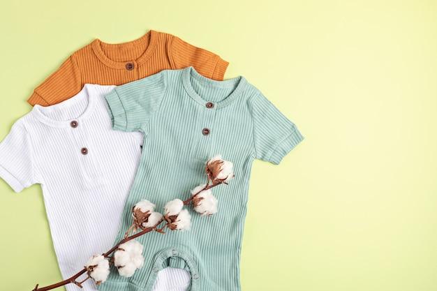Prenda de bebé de género neutro. ropa de algodón orgánico, moda recién nacida, branding, idea de pequeña empresa. endecha plana, vista superior