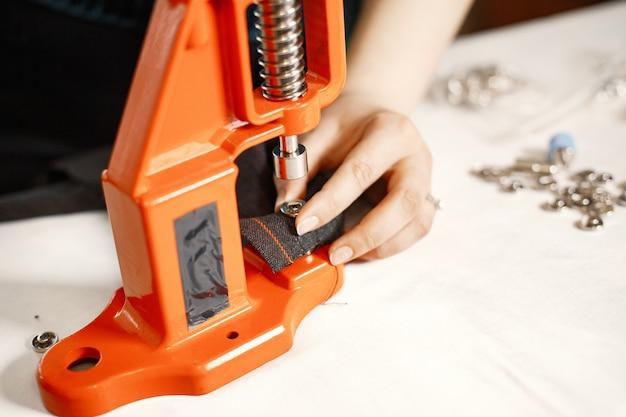 Prensa naranja para ropa. botones sobre tela. mujer con herramientas de costura