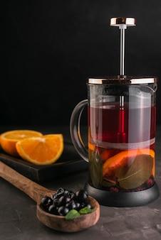 Prensa de té con rodajas de naranja