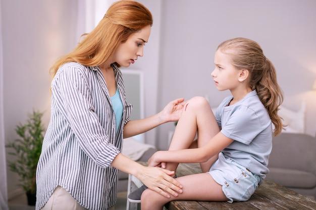 Preocupación de las madres. agradable madre preocupada mirando la rodilla de sus hijas mientras está conmocionada