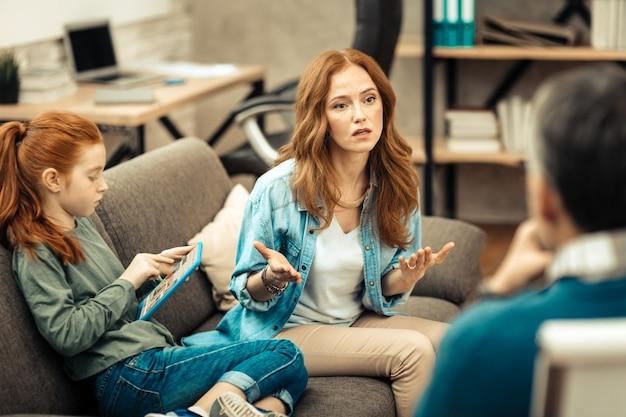 Preocupación de los padres. bonita mujer ansiosa mirando al psicólogo mientras habla de su hija