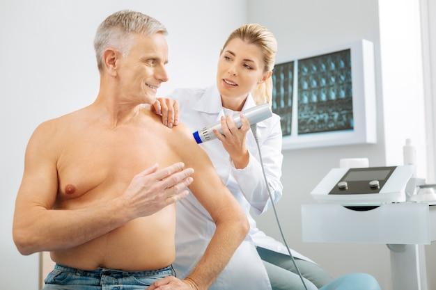 Preocupación por la salud. encantado de anciano positivo sentado en la cama y haciendo una pregunta a su médico mientras es examinado