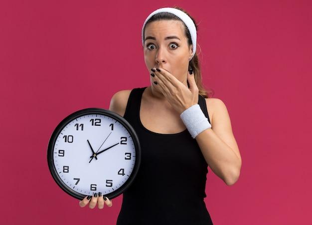 Preocupada joven bastante deportiva vistiendo diadema y muñequeras sosteniendo el reloj manteniendo la mano en la boca