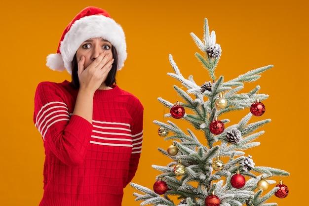Preocupada joven con gorro de papá noel de pie cerca del árbol de navidad decorado manteniendo la mano en la boca otra detrás de la espalda mirando a la cámara aislada sobre fondo naranja