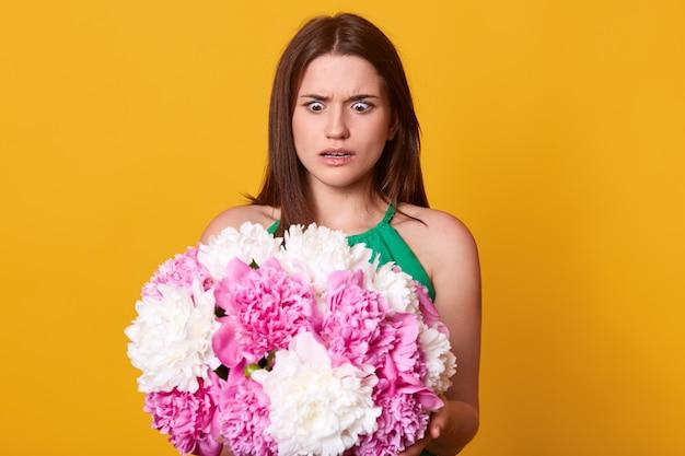 Preocupada mujer joven sorprendida mirando flores rosas y blancas con sorpresa, sosteniendo peonías en ambas manos, abriendo los ojos ampliamente