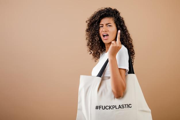 Preocupada mujer negra milenaria con mensaje de plástico ecológico a la mierda en una bolsa aislada sobre marrón
