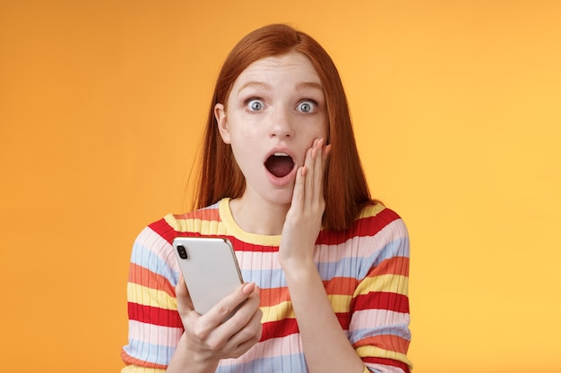 Preocupada, sorprendida, emotiva chica pelirroja descubre noticias impresionantes mirar cámara caída mandíbula jadeando impresionado toque mejilla sostener teléfono inteligente terminar de leer impresionante historia inquietante, fondo naranja