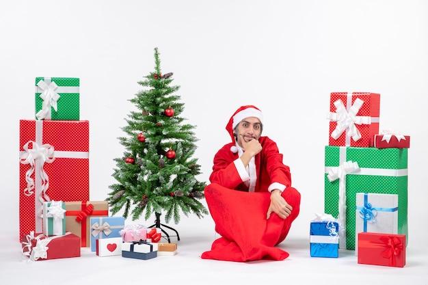 Preocupado adulto joven reflexivo vestido como papá noel con regalos y árbol de navidad decorado sentado en el suelo sobre fondo blanco.