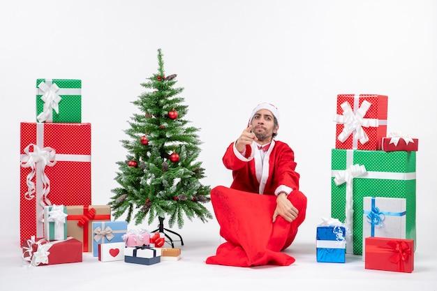 Preocupado adulto joven vestido como papá noel con regalos y árbol de navidad decorado sentado en el suelo sobre fondo blanco.
