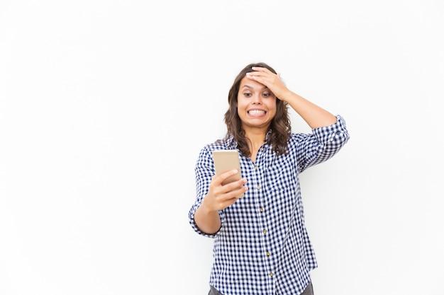 Preocupado, avergonzado usuario de un teléfono inteligente cometiendo un error