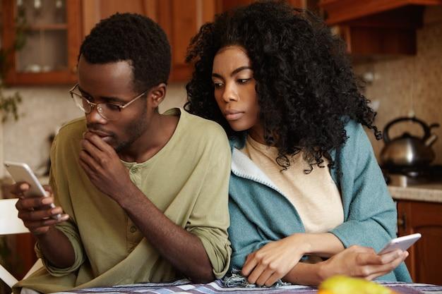 Preocupado joven afroamericano con gafas escribiendo sms en el teléfono inteligente sumido en sus pensamientos sin darse cuenta de que su novia está espiando, mirando por encima del hombro, tratando de leer lo que está enviando mensajes de texto