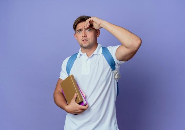 Preocupado joven apuesto estudiante vistiendo bolsa trasera sosteniendo libros y poniendo la mano en la frente aislada en la pared azul