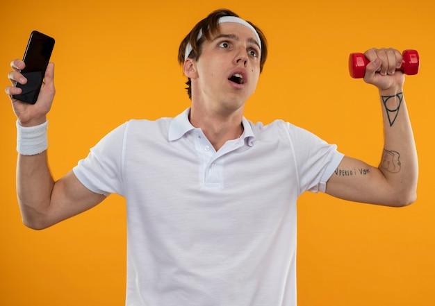 Preocupado joven deportivo vistiendo diadema y muñequera levantando teléfono con mancuerna aislado en pared naranja