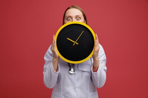 Preocupado joven doctora rubia vistiendo bata médica y estetoscopio alrededor del cuello sosteniendo el reloj detrás de él