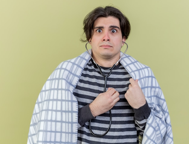 Preocupado joven enfermo envuelto en plaid vistiendo y escuchando sus propios latidos con estetoscopio aislado sobre fondo verde oliva