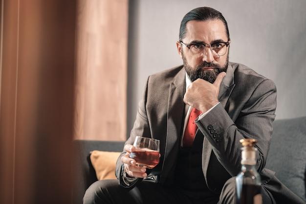 Preocupado por los negocios. hombre de pelo oscuro con barba bebiendo whisky sintiéndose preocupado por el negocio