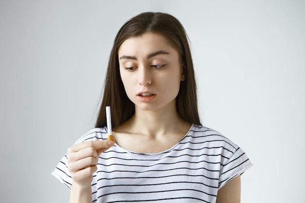 Preocupado perplejo joven mujer morena vistiendo camiseta casual sosteniendo un cigarrillo