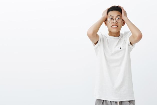 Preocupado preocupado y nervioso preocupado apuesto chico asiático presionando las manos a la cabeza inclinándose hacia atrás y apretando los dientes en pánico estando en una situación de perplejidad