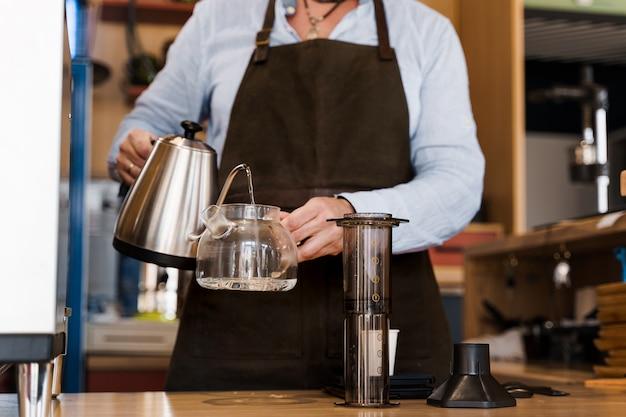 Preparación alternativa de café aeropress por barista en la cafetería