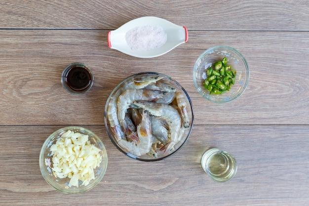 Preparación antes de cocinar camarones salteados con ají, ajo y sal en mesa de madera. vista superior o endecha plana.