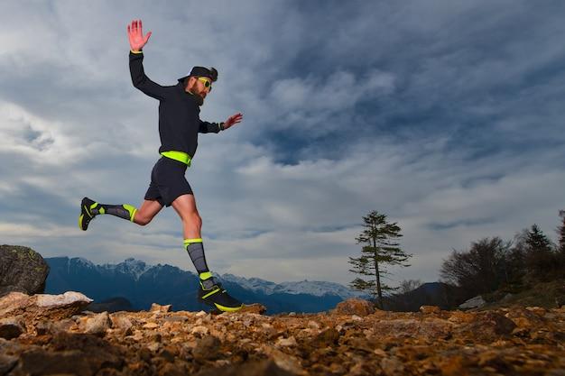 Preparación atlética de un hombre para competiciones de trail running en las montañas