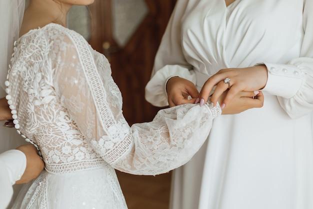 Preparación de la boda, vestir a la novia para la ceremonia de la boda, vista frontal de la vestimenta de la boda
