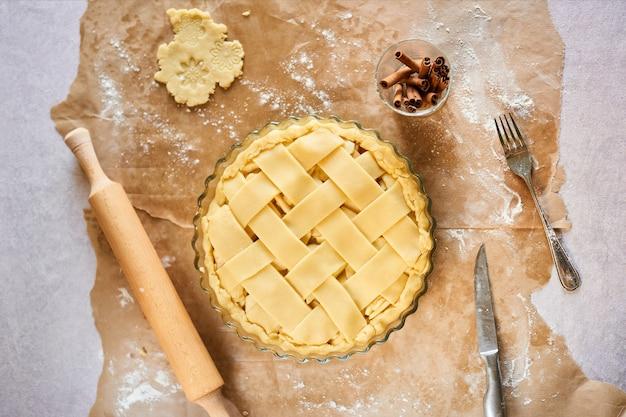 Preparación casera rústica de la empanada de manzana en la cocina blanca. endecha plana.