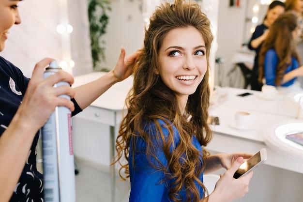 Preparación para celebrar en el salón de belleza de la modelo atractiva feliz sonriendo al estilista