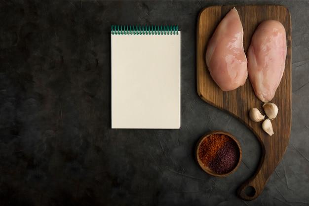 Preparación de cocción de pechuga de pollo con un libro de cocina a un lado