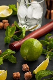 Preparación de cóctel mojito. utensilios de barra e ingredientes menta, lima, hielo y azúcar de caña. vista superior con espacio de copia