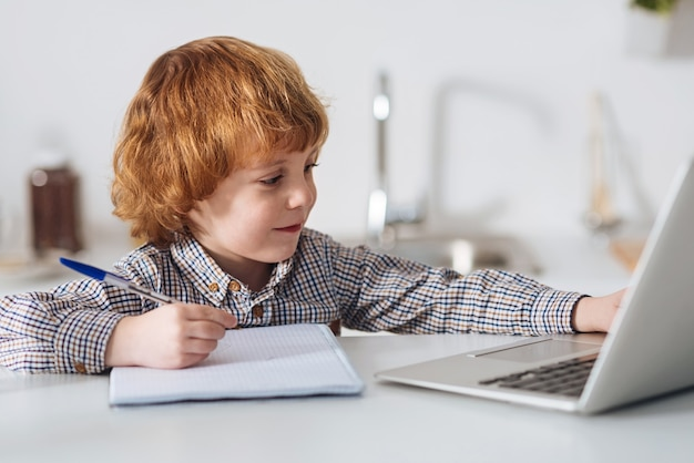 La preparación como arma principal. niño brillante inteligente comprometido leyendo un libro en su computadora portátil y haciendo notas mientras está sentado en la mesa de la cocina