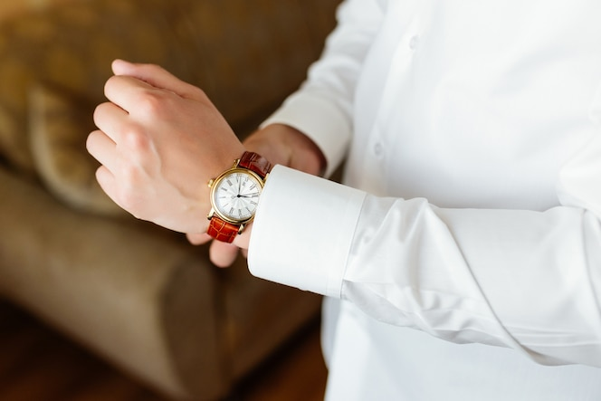Preparación de ensayo el reloj del novio en la mano.