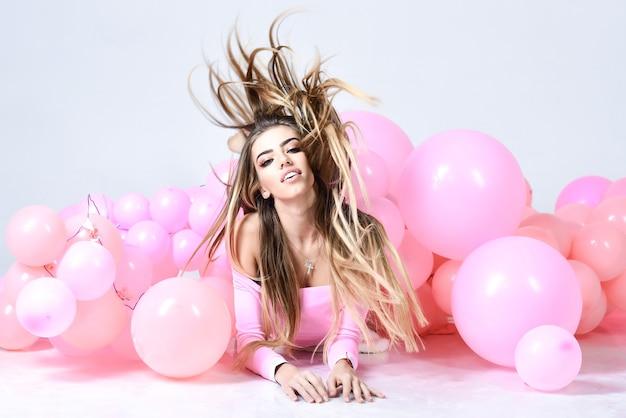 Preparación para fiesta de cumpleaños. hermosa chica con cabello largo. mujer feliz con globos de colores.
