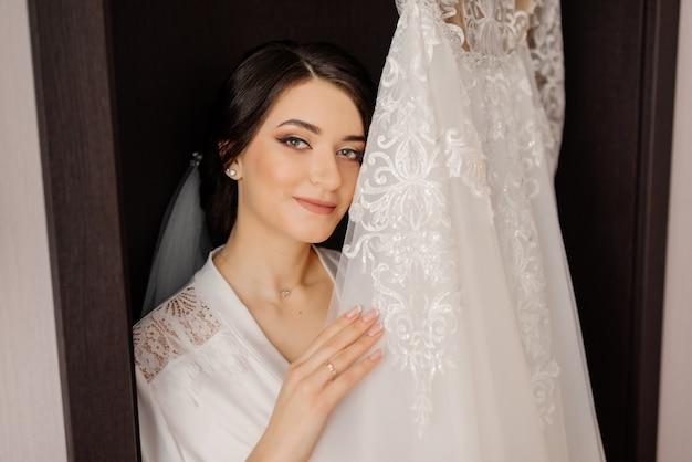 Preparación de la mañana de la boda. feliz novia con su vestido de novia. retrato de la mañana de novia