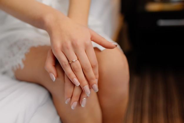 Preparación de la mañana de la boda. feliz novia tiene las manos sobre las rodillas muestra anillo de compromiso