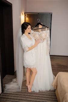Preparación de la mañana de la boda. feliz novia tiene en sus brazos y mira su vestido de novia.