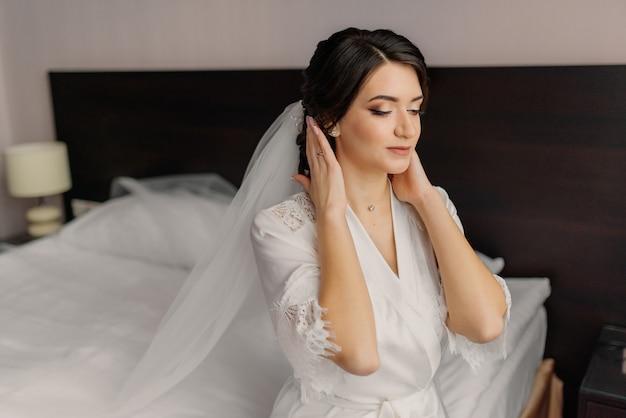 Preparación de la mañana de la boda. retrato de novia en la mañana de la boda. la novia toca su peinado y se regocija.