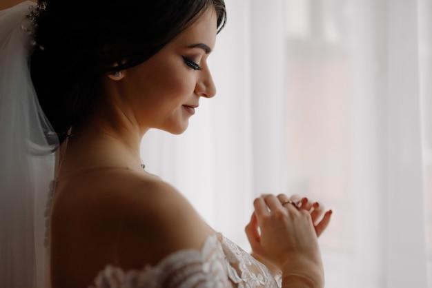 Preparación de la mañana de la boda. retrato de novia la novia feliz toca su anillo de compromiso.