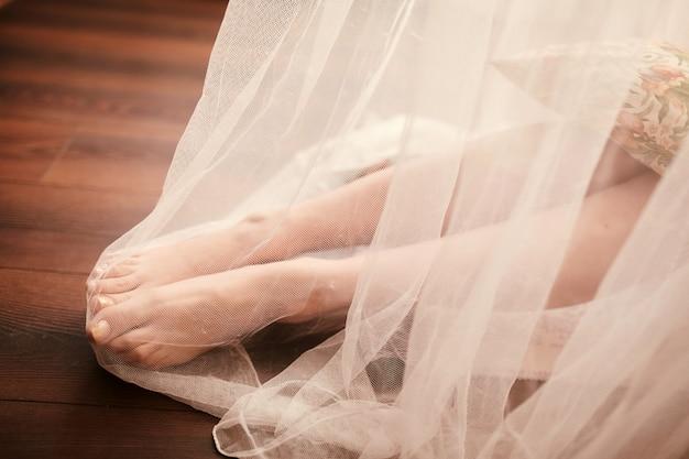 Preparación de la mañana de la novia. piernas de la novia en velo blanco sobre suelo de madera.