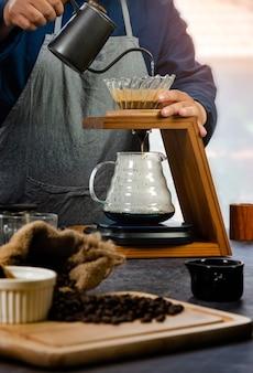 Preparación manual de café por goteo. barista vierte agua sobre café molido, filtro de papel y lo recoge en recipiente de vidrio colocado debajo de un soporte de madera.