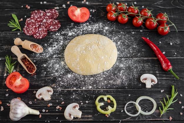Preparación de la masa y hortalizas para producción de pizza. ingredientes para la producción de pizza sobre un fondo de madera.
