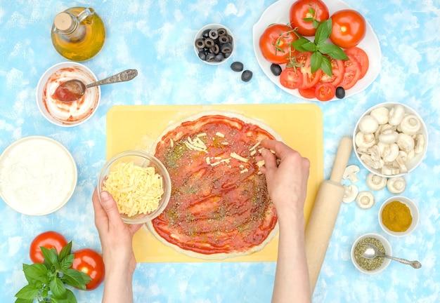 Preparación paso a paso de pizza vegetariana casera, paso 5 - agregue queso rallado a la salsa