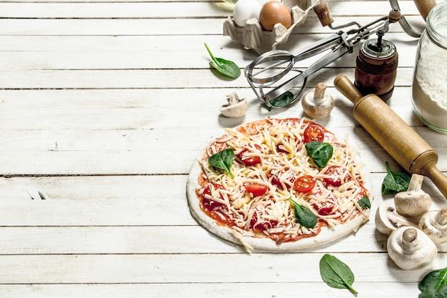 Preparación de pizza con diversos ingredientes en mesa de madera blanca.