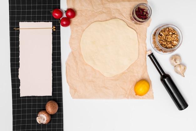 Preparación de pizza italiana casera rodeada de ingredientes y papel en blanco.